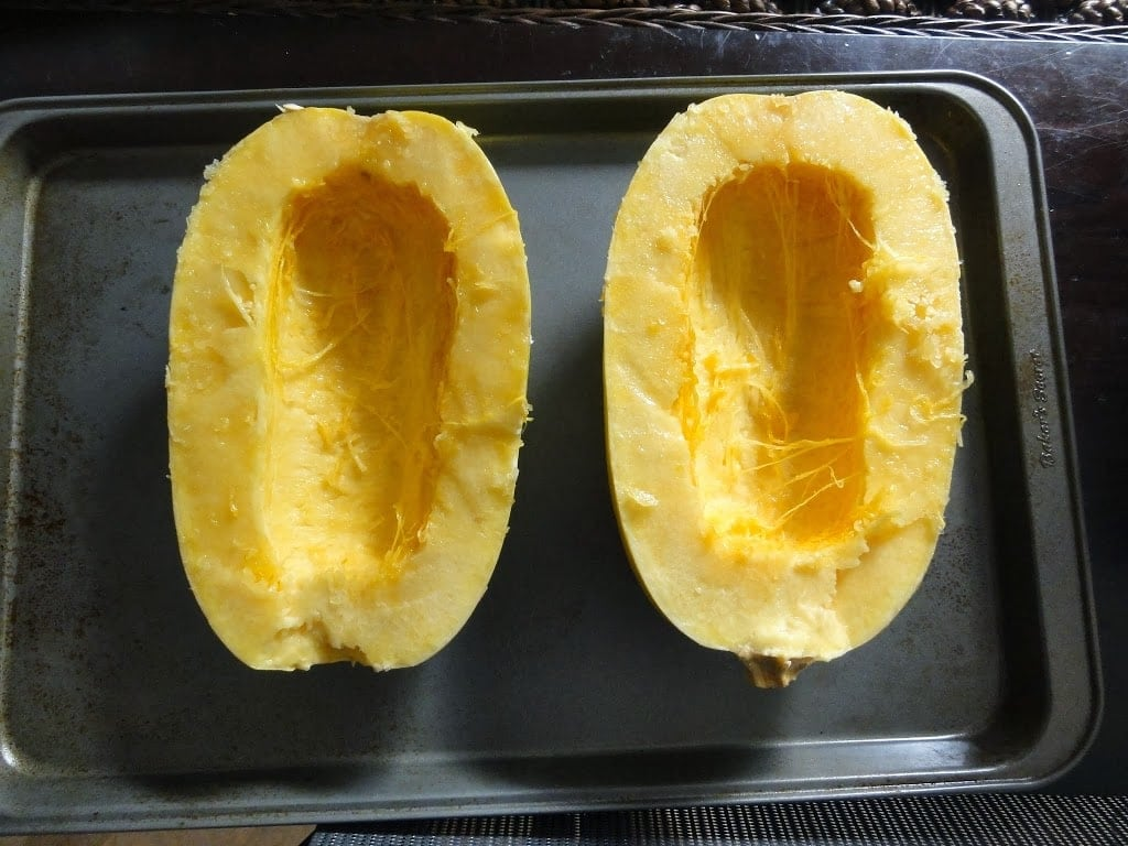 Two halves of a squash prepared to be put in the oven