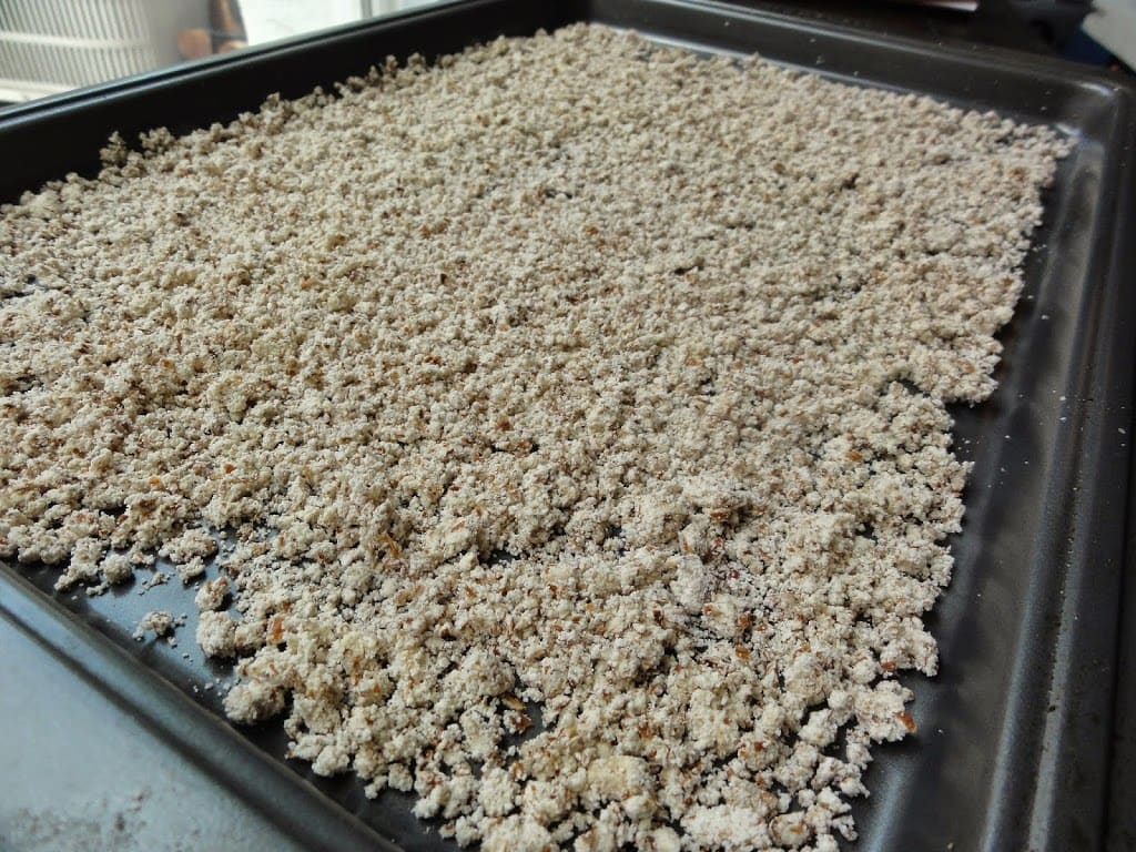 almond pulp spread out on a pan after dehydration