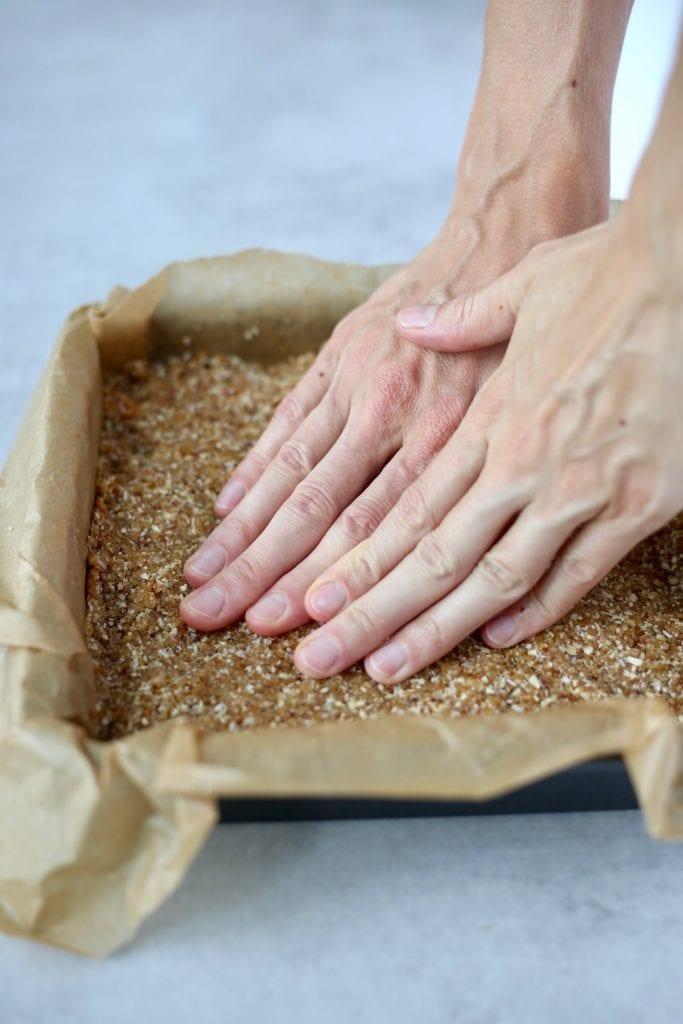 Pressing dough into a pan for granola bars