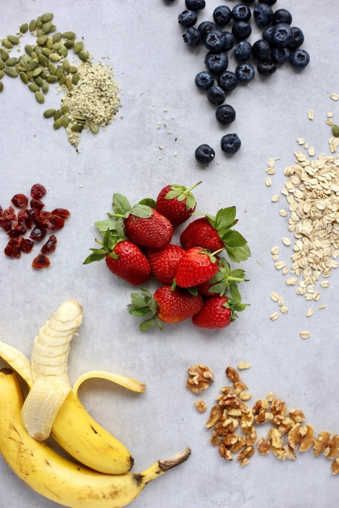 Berries, bananas, nuts, seeds, oats and dried fruit beautifully displayed on a table
