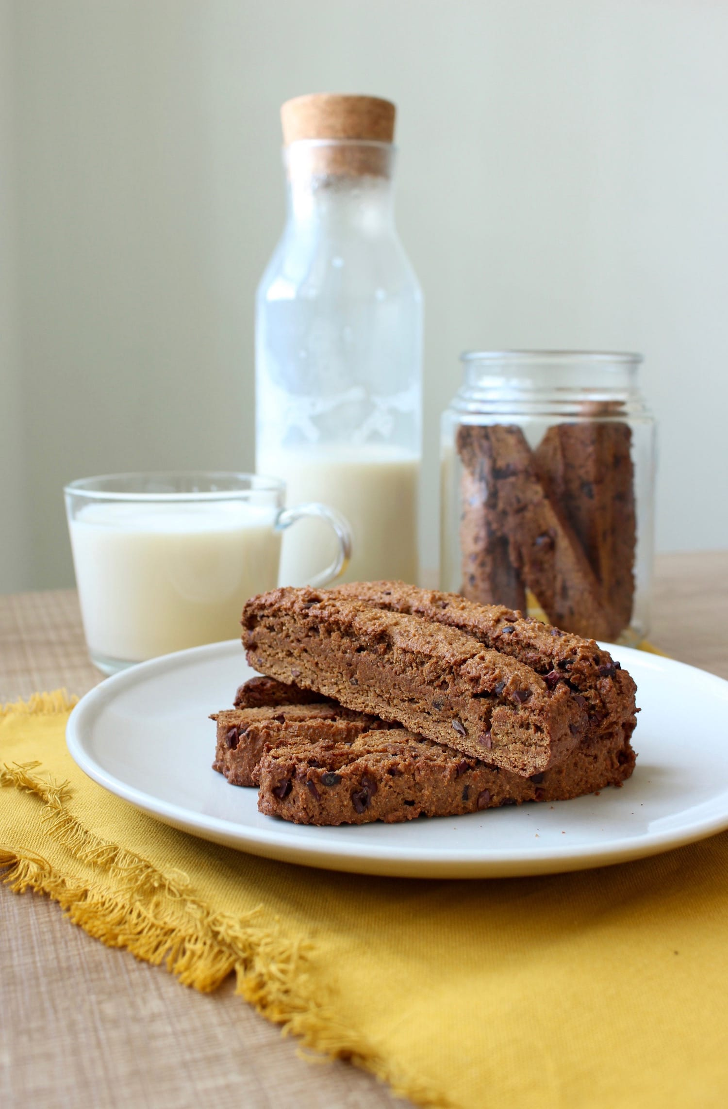 Vegan Pumpkin Chocolate Chip Biscotti stacked on a plate served with milk