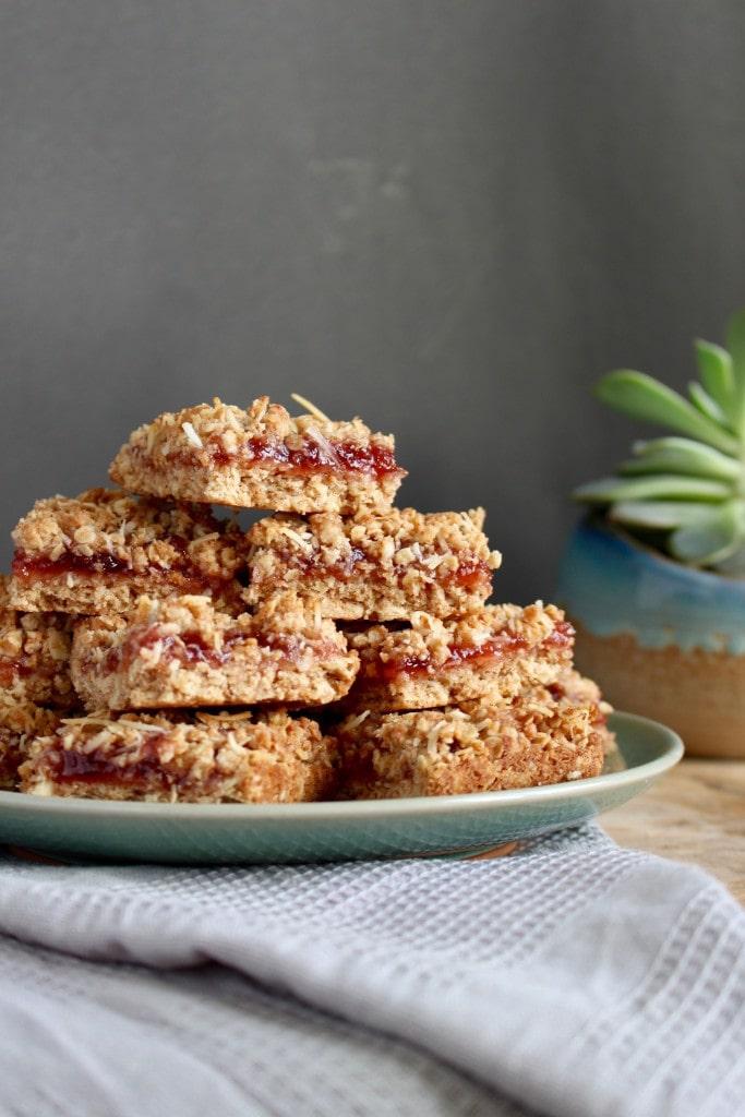 Vegan strawberry jam oatmeal bars piled high on a plate