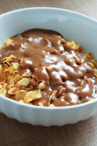 peanut butter sauce being mix into cornflakes