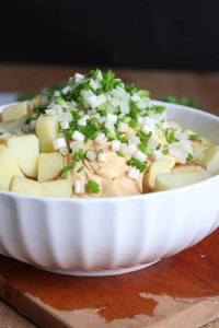 green and white onions on top of potatoes