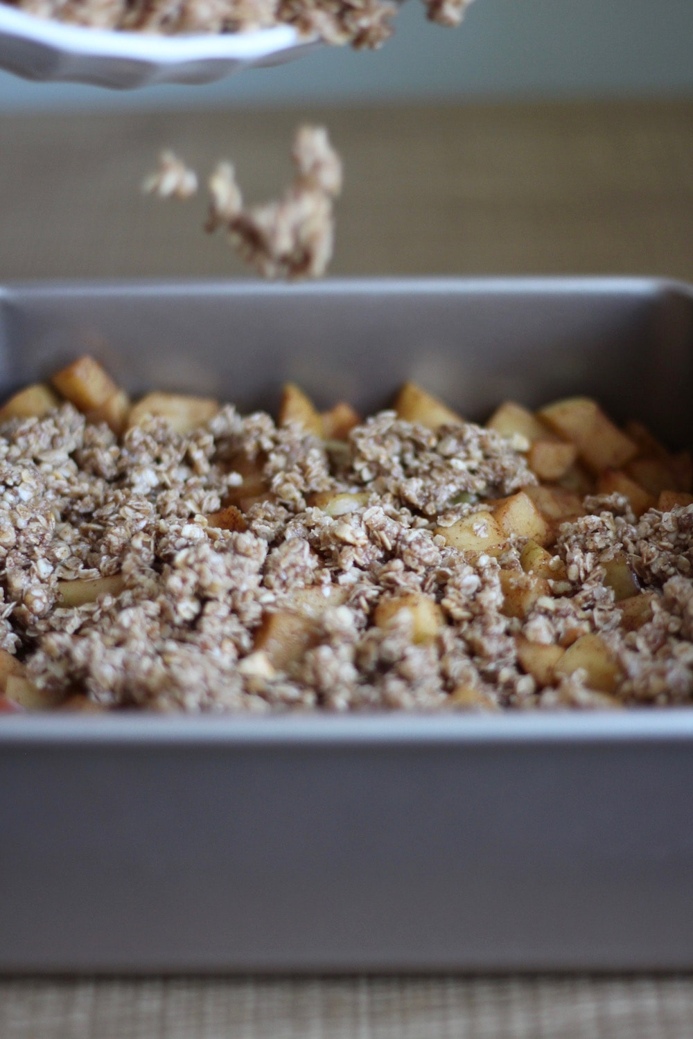 healthy crumb topping being sprinkled over apples for vegan apple crisp