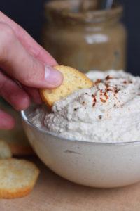 A cracker scooping up Okara (soy milk pulp) hummus