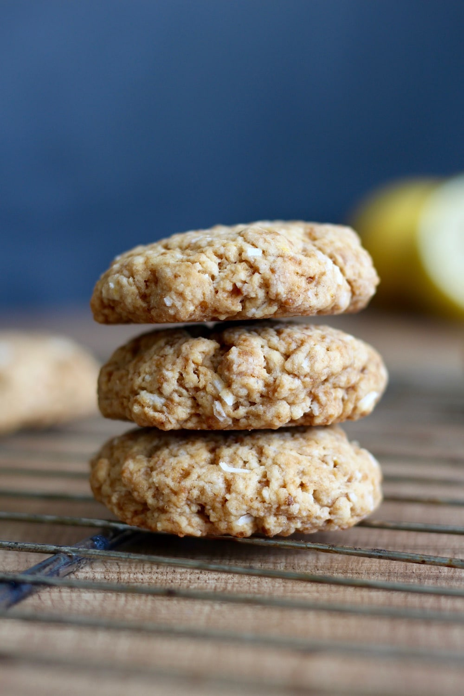 vegan lemon coconut cookies stacked on a wire rack