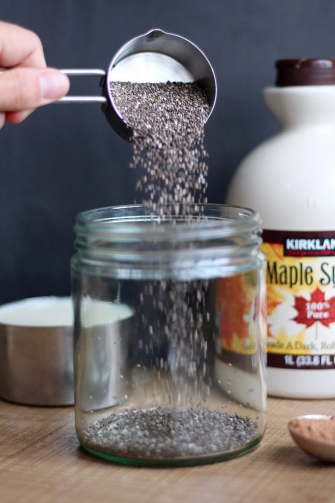 chia seeds being poured into a glass jar