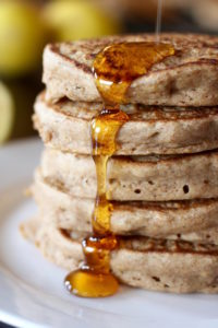 Maple syrup running down a stack of vegan lemon yogurt pancakes