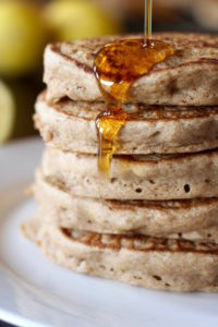 Maple syrup being poured on a stack of Vegan Whole Wheat Lemon Yogurt Pancakes