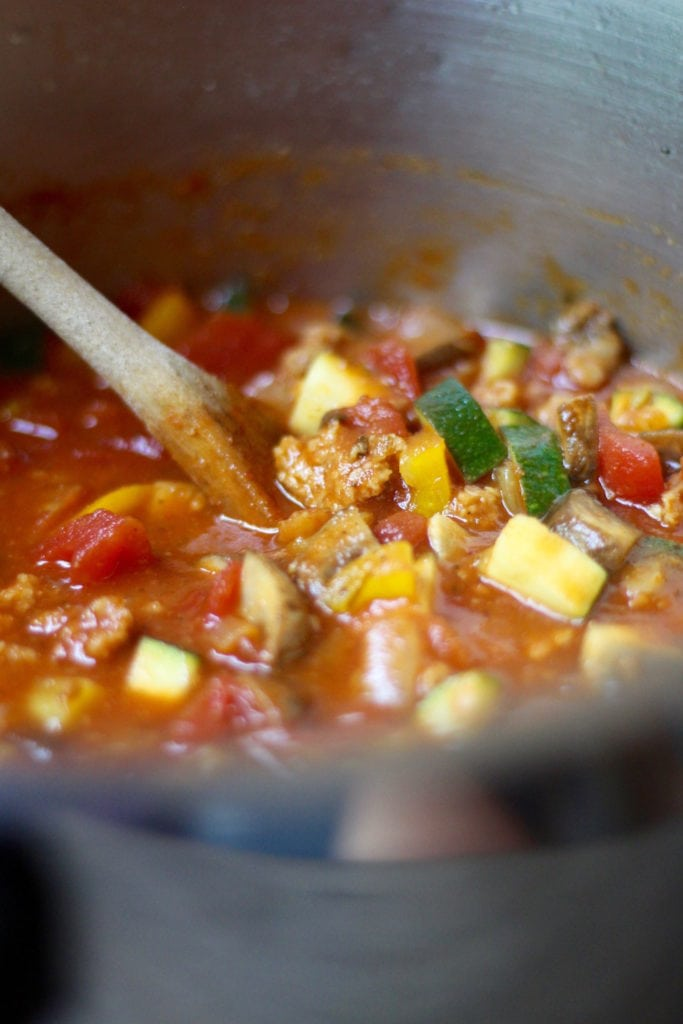 vegan pizza soup with wooden spatula