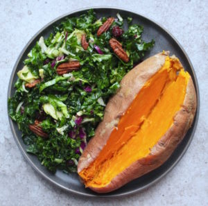 Green cruciferous salad paired with a baked sweet potato on a plate