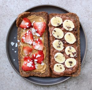 toast topped with cashew butter and strawberries and chocolate yogurt spread