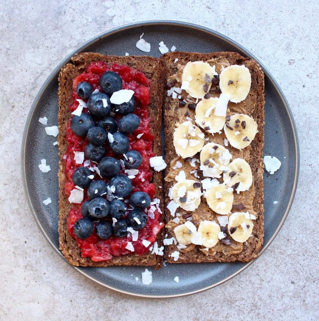 Toast topped with strawberry jam and blueberries and almond butter and banana