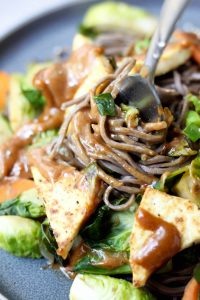 A fork twirling almond butter soba noodles