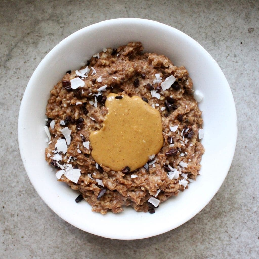 Chocolate Zucchini oatmeal made in a microwave and topped with nut butter