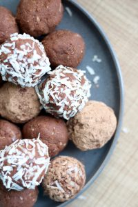 Almond Pulp Freezer Brownie Bites rolled in coconut flakes and cacao powder