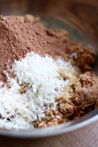 coconut flakes, cocoa powder and almond pulp in a mixing bowl