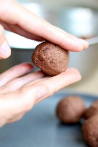 Rolling almond pulp freezer brownie bites into balls
