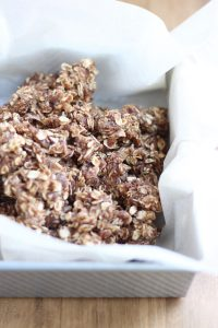 Chewy Almond Butter Date Granola Bars in a parchment paper lined baking dish