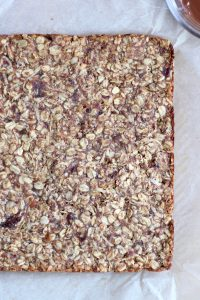 Chewy almond butter date granola bar dough packed into a baking dish