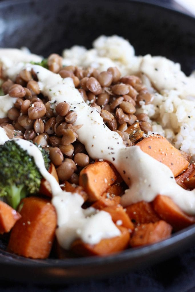 buddha bowl with carrots broccoli rice and vegan miso tahini dressing