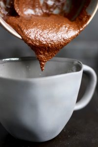 chocolate mug cake batter being poured into a mug
