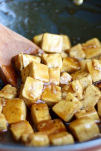 Orange tofu being stirred with wooden spoon in a pan