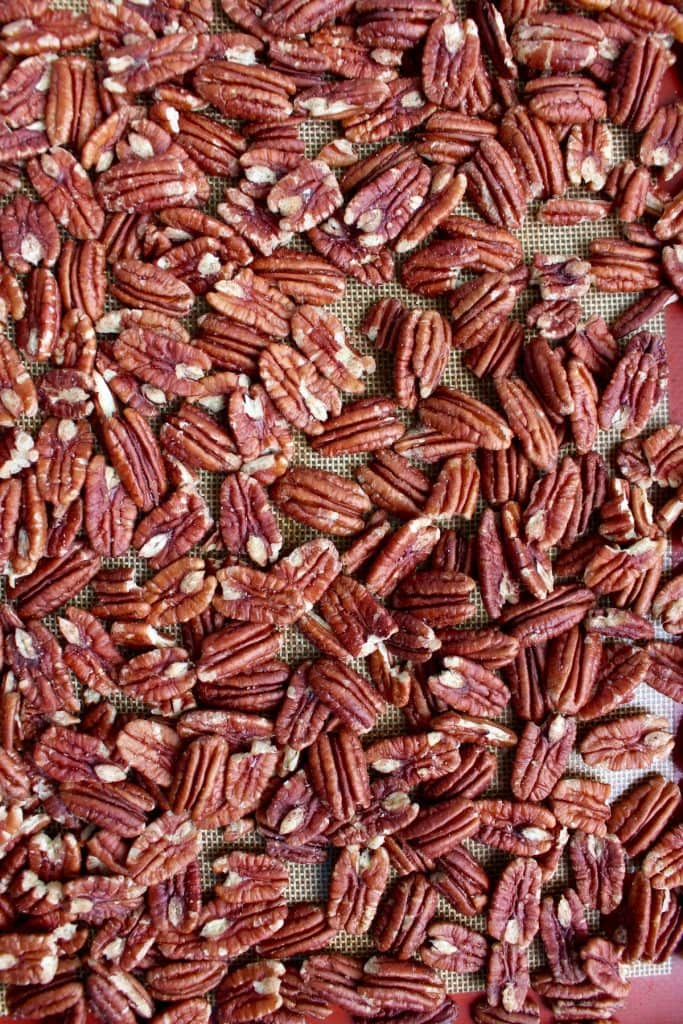 Pecans spread out on a baking tray for toasting