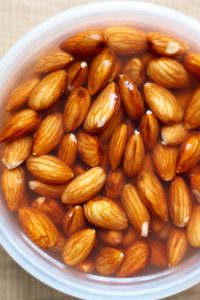 Almonds soaking in tupperware for homemade almond milk