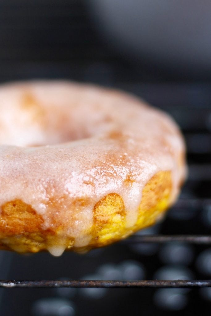 A glazed pumpkin baked donut drying on a wire rack