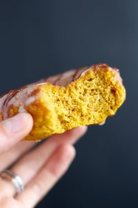 a bite taken out of a pumpkin baked donut