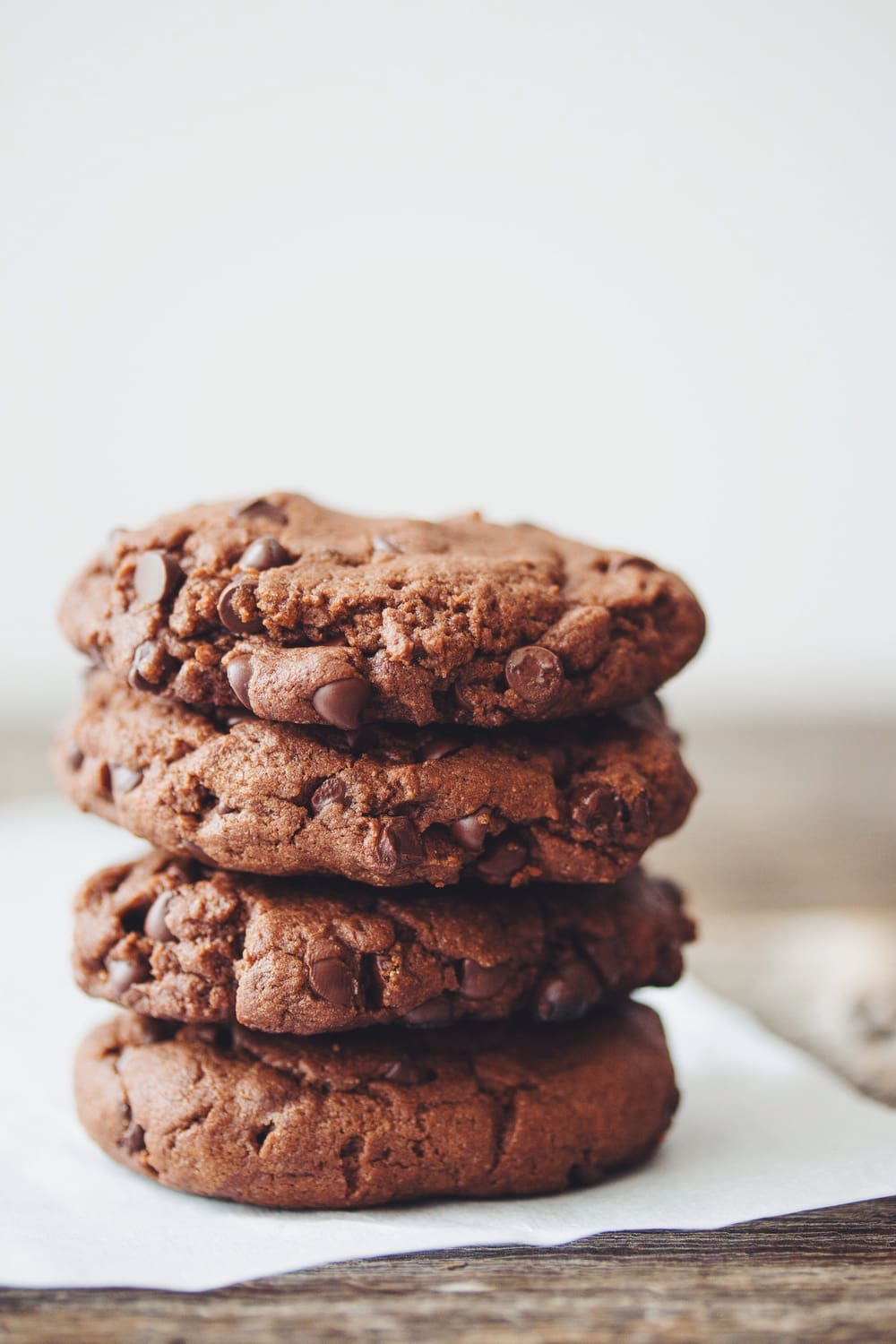 double chocolate cookies stacked on parchment paper