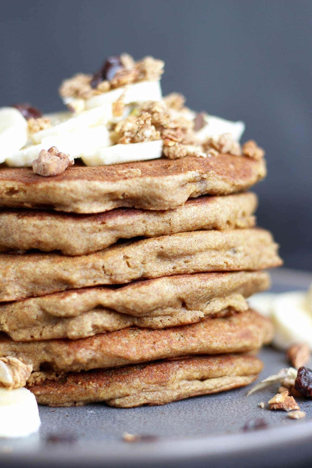 A tall stack of gluten free banana pancakes topped with banana and granola