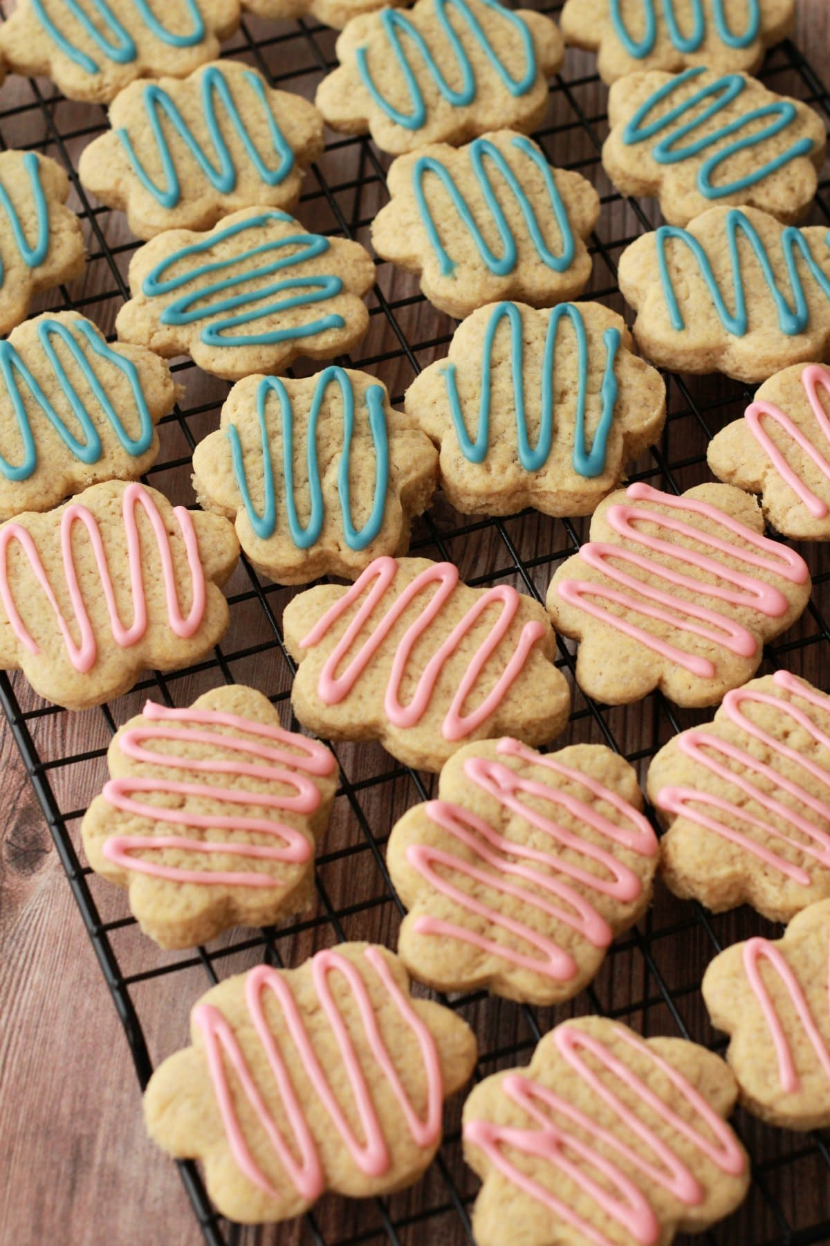 frosted sugar cookies cooling on a wire rack