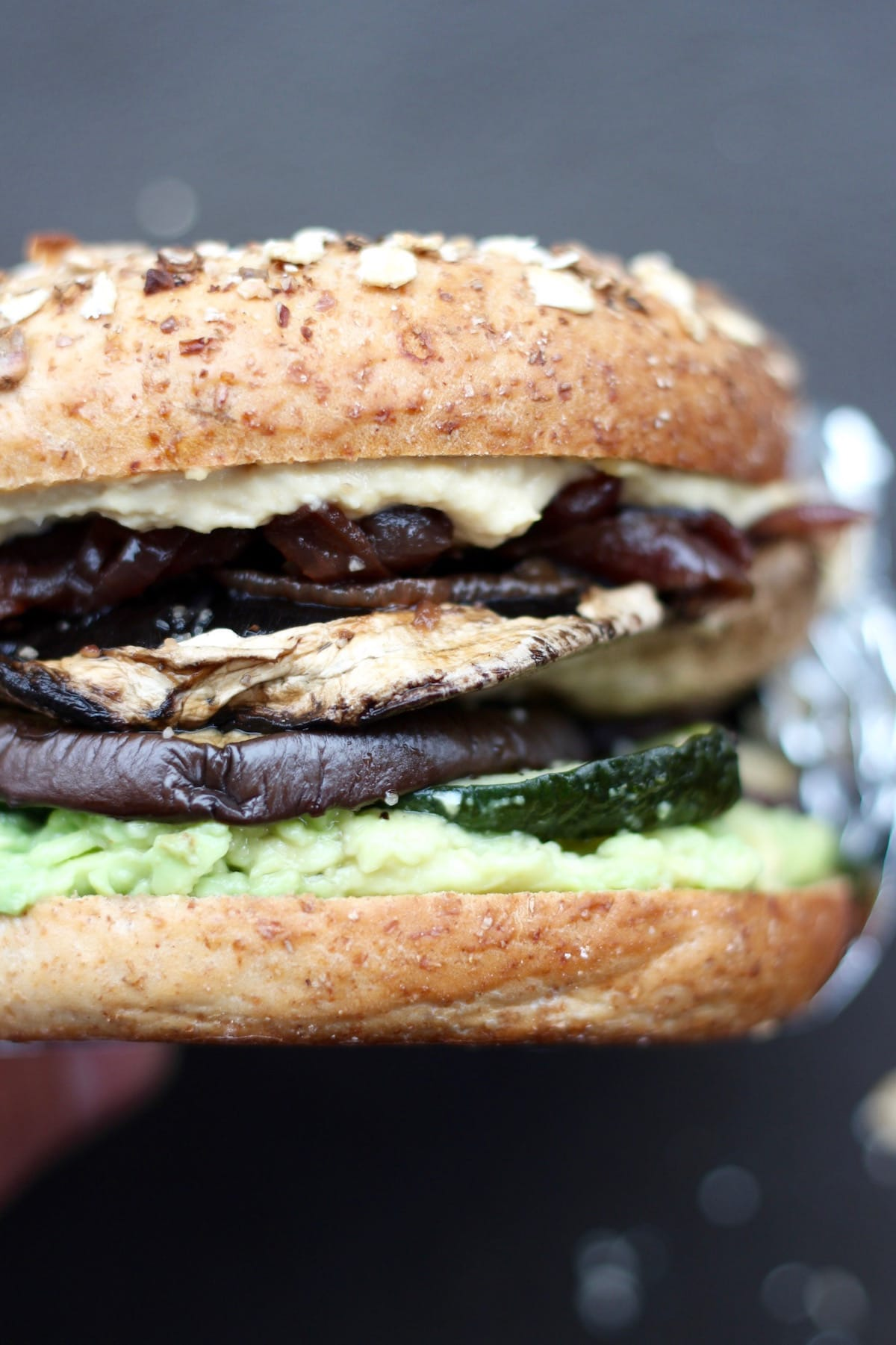 A loaded roasted veggie and hummus bagel sandwich