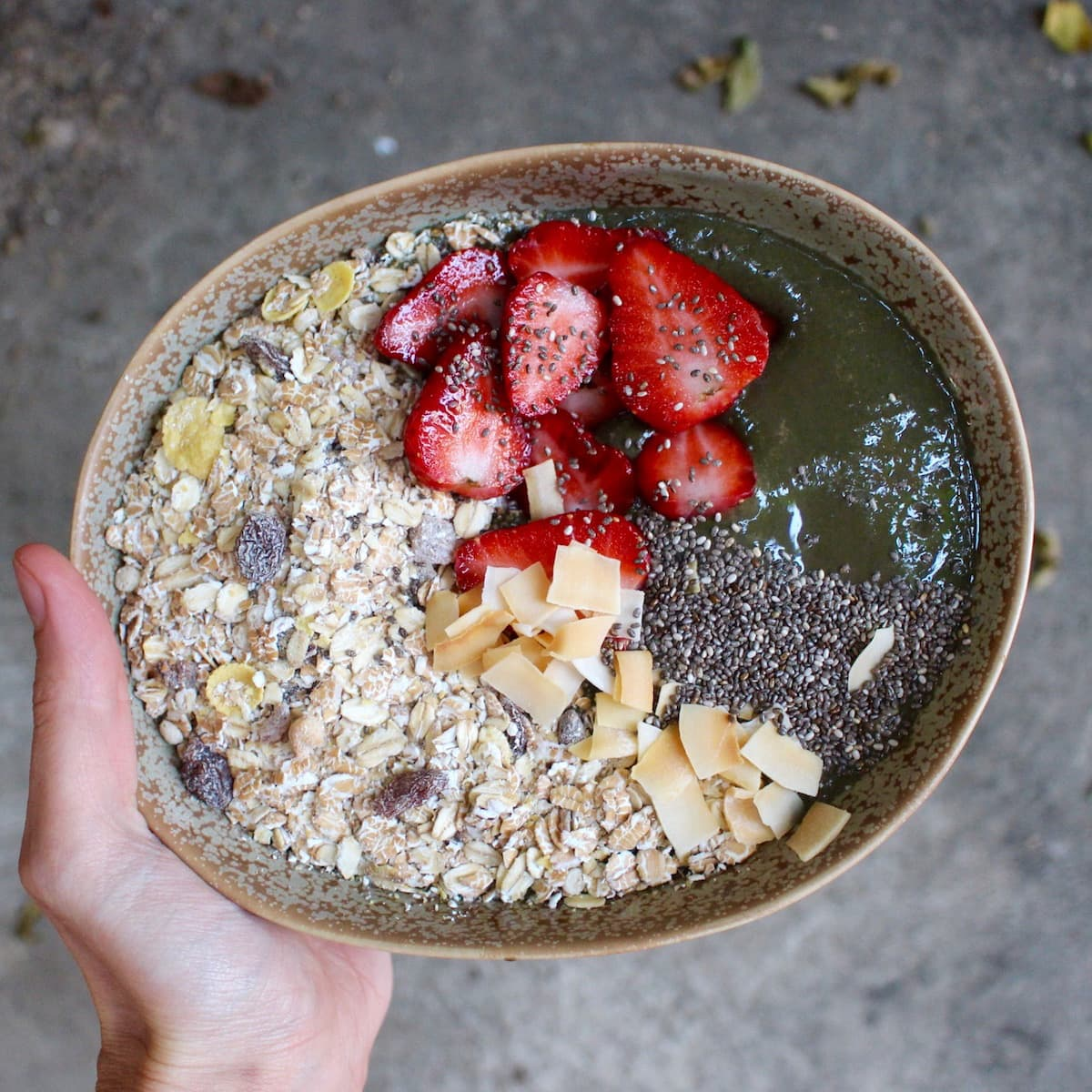 chocolate green smoothie bowl topped with muesli and fruit