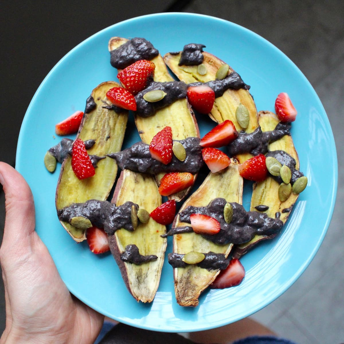 sweet potatoes topped with black tahini and berries