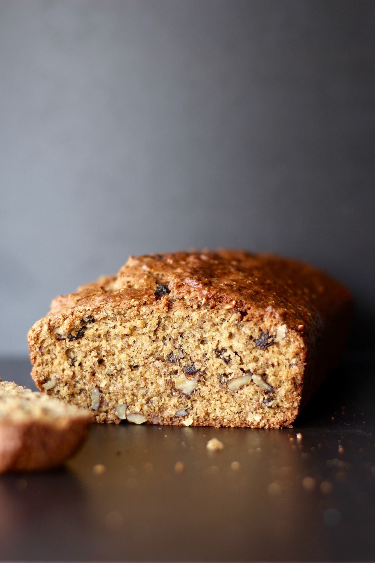 walnuts and raisins peeking out of a sliced loaf of quick bread