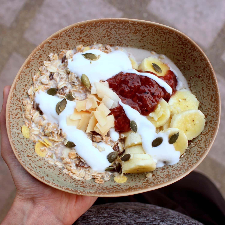 muesli, coconut yogurt, strawberry jam and banana
