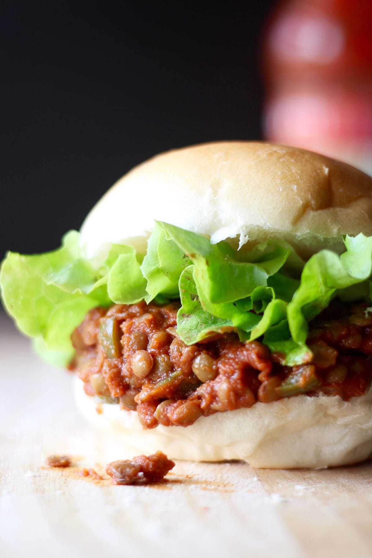 lentil sloppy joes spilling out of a soft hamburger bun