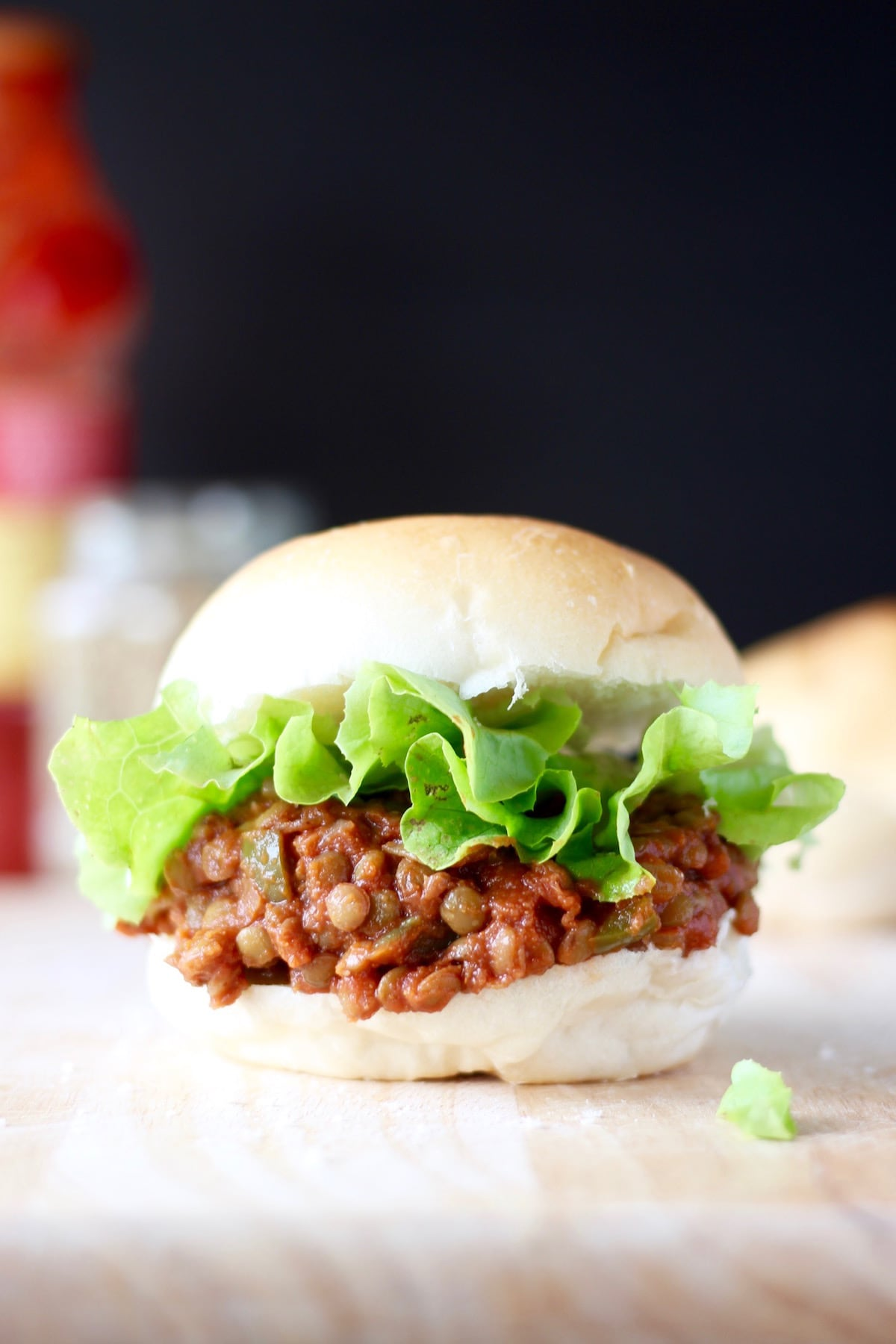 Lentil sloppy joes piled high on a hamburger bun with lettuce