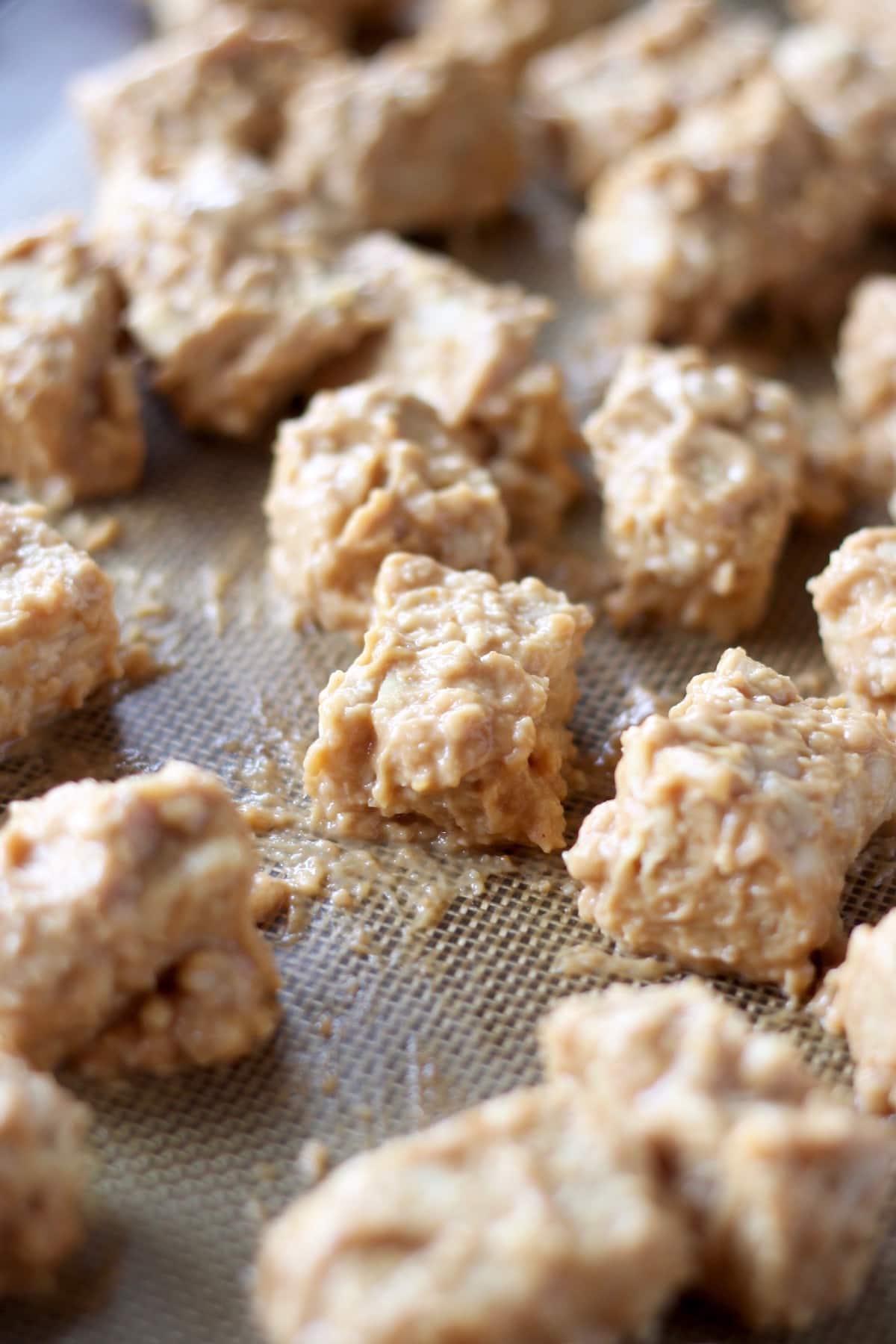 peanut orange sauce coated tempeh bites arranged on a baking tray