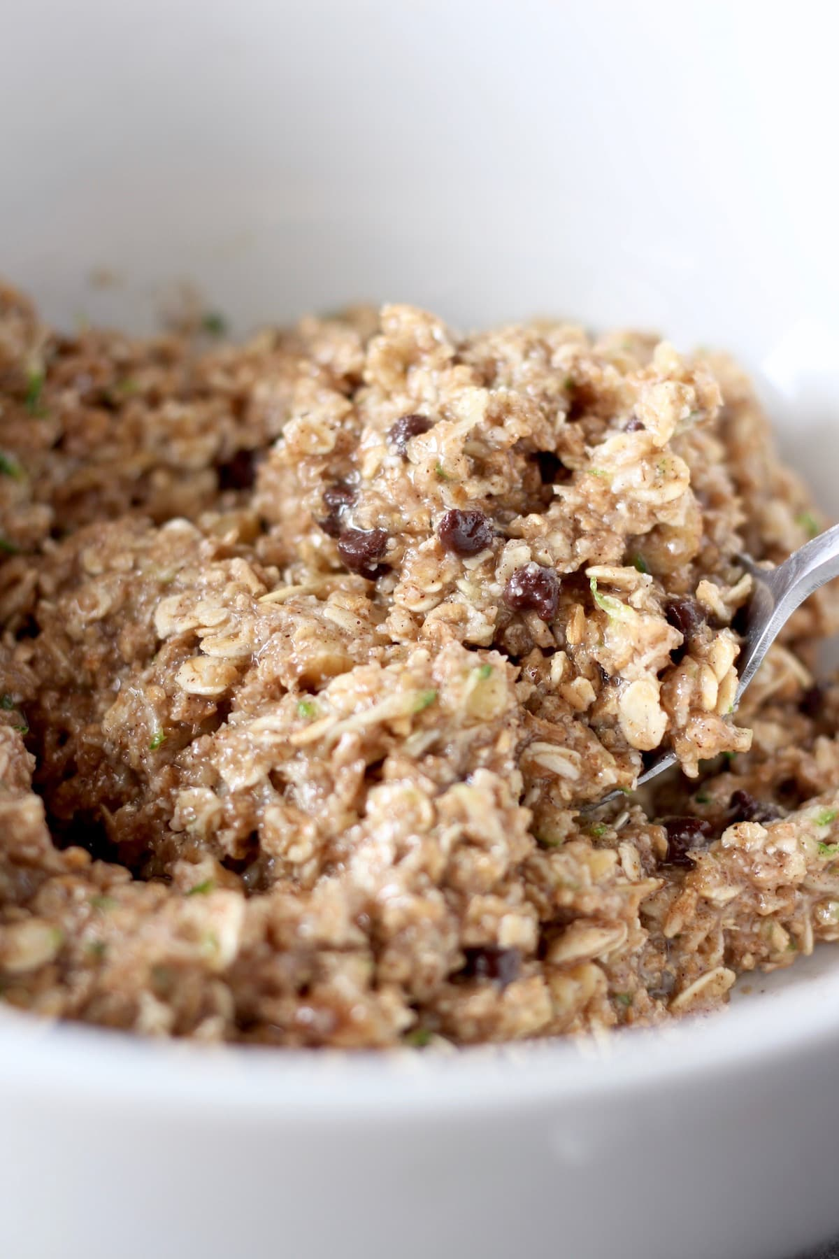 zucchini oatmeal cookie dough being mixed in a bowl