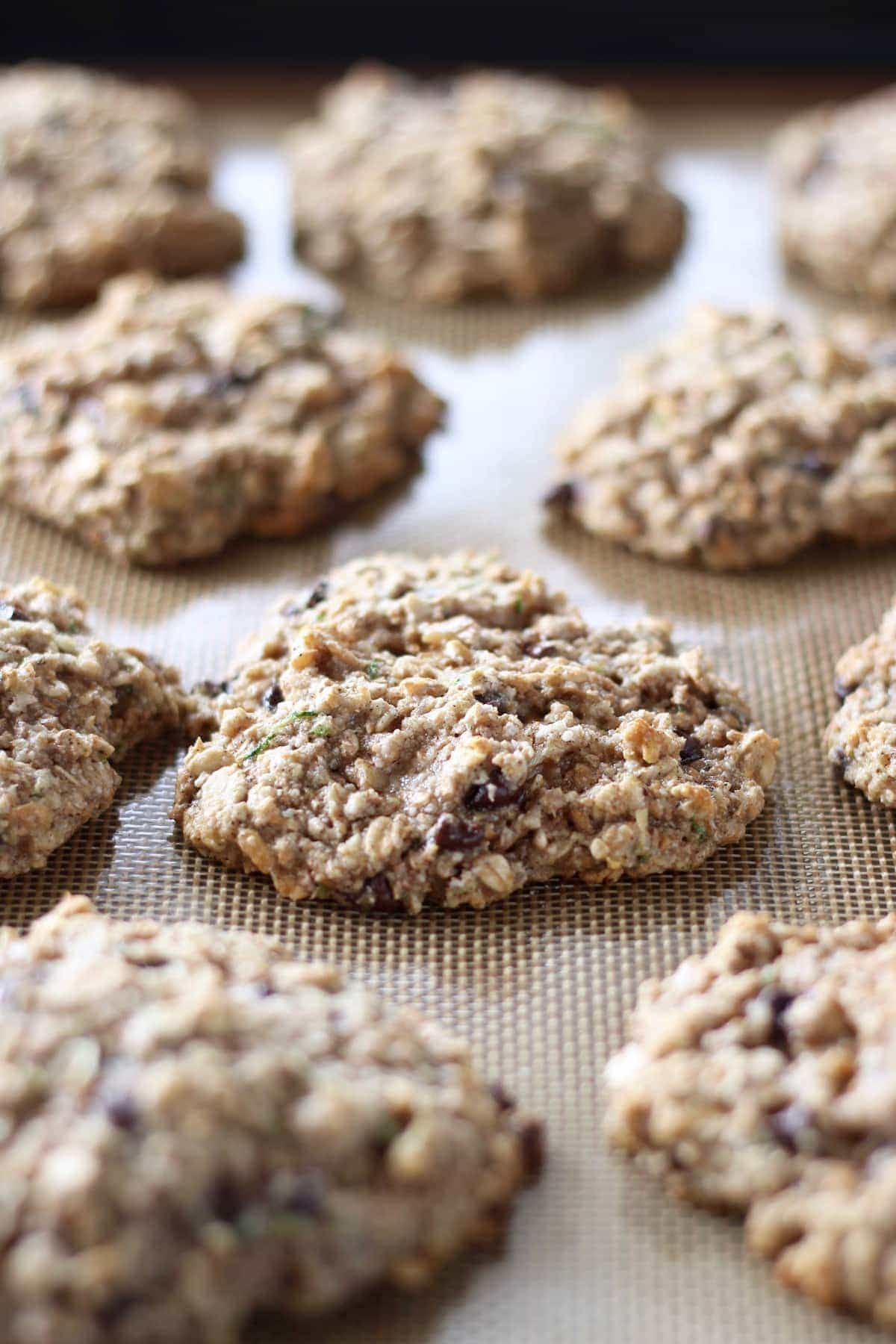 zucchini oatmeal cookies cooking on a silicone baking mat
