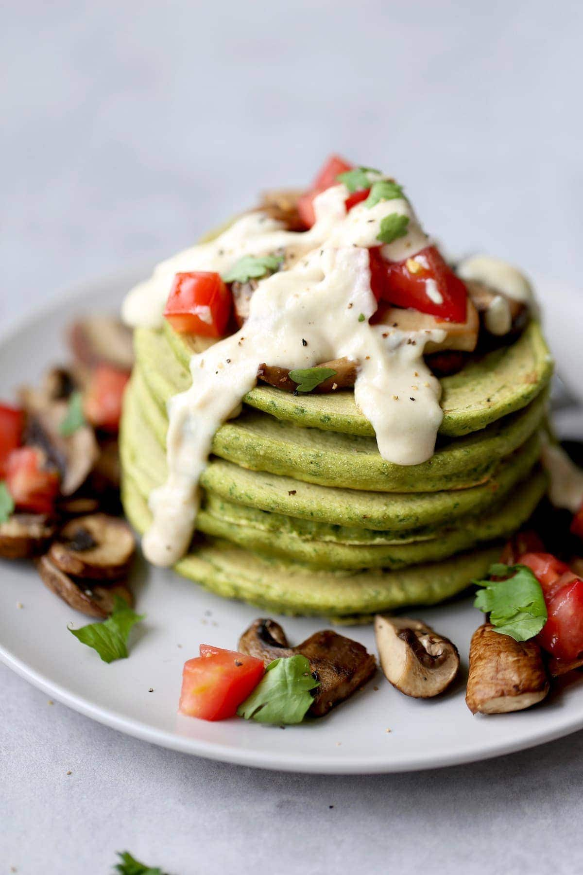 a stack of chickpea flour falafel pancakes topped with tahini sauce