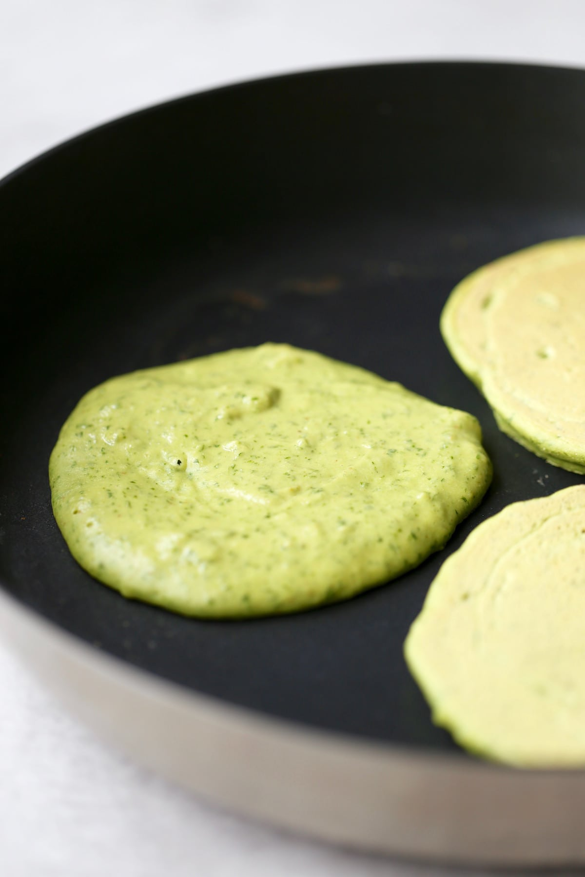 chickpea flour pancakes cooking on a skillet