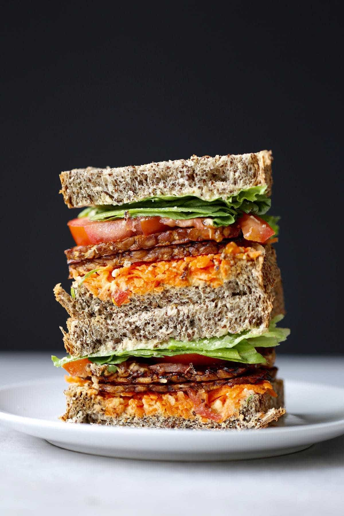 a loaded colorful tempeh bacon sandwich
