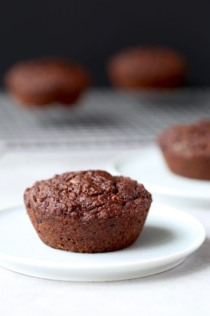 a jumbo vegan chocolate muffin on a plate that is also gluten free