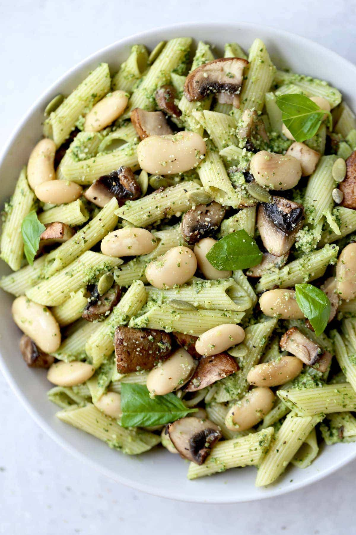 pesto pasta topped with butter beans, basil and mushrooms